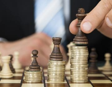 Midsection of businessman placing chess pieces on stacked coins