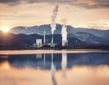 Coal-fired power plant destroying the environment with releases. Plant is reflected in the lake.