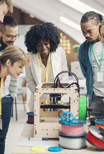 Diversity startup business team working together by 3D printer. Looking at 3D printer printing and discussing.