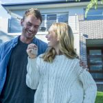 Young couple holding their new house key. They are standing in front of the home in casual clothes. Both are happy, relaxed and smiling. He has a beard and she is blonde. They could be buying or selling real estate. Copy space
